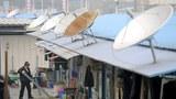 2008年法新社图片:四川汶川地震后灾民临时住处。棚屋上架着卫星天线。(AFP PHOTO/LIU Jin)