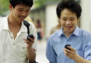 广州街头使用手机的年轻人。(法新社)