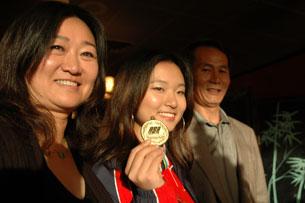 美國射擊國家隊的華裔選手施韻和母親樊煜,父親施也林合影。(粵語部何山拍攝)