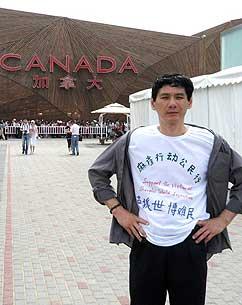 """张晓刚穿著写有""""马上行动声援世博难民""""的文化衫在上海世博园加拿大馆前。(图片来源:盛雪提供)"""