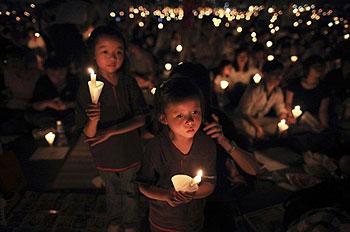 2011年6月4日晚,香港15万市民在维园举行烛光纪念会纪念北京天安门64屠杀22周年,一如往年,许多家长带著他们年幼的孩子一起参加集会。(法新社图片)