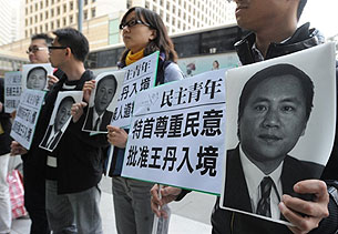 1月26日,香港示威者手持王丹的照片,要求当局准许他入境参加司徒华的追思会。(法新社图片)