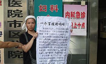 被打伤后,死者的女儿仍然坚持在医院门口举牌抗议。(欧忠勇 提供)