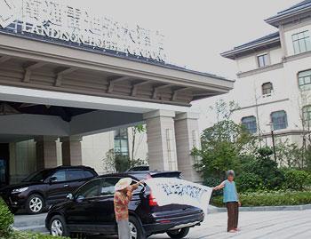 """南通拆迁户周一早上(8月8日)在酒店外拉上""""拉出去,我们就不管了""""的横幅抗议。(拆迁户徐梅提供)"""