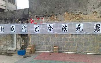 薛锦波虽已入土为安,但村民的土地问题仍未解决,村民仍在村内高挂抗议横额。(村民张先生提供)