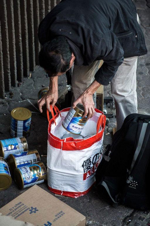 2013年1月29日,一位大陸遊客在香港上水車站整理攜帶大批嬰兒奶粉的行李。(AFP PHOTO/Philippe Lopez)