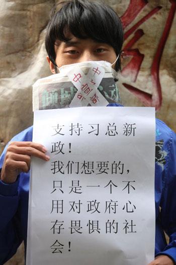 """1月10日(星期四),一位來自廣州大學的學生中印有""""中宣部""""的字條封住自己的嘴巴,站在南方傳媒大廈前聲援南方週末。(法新社Jonathan Wu/EyePress)"""