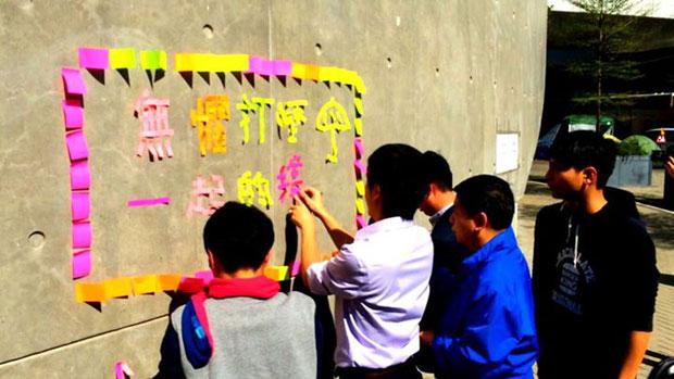 """12月31日,香港民主党成员声援涉嫌涂鸦的14岁女童,在金钟""""连侬墙""""用便利贴纸砌出""""无惧打压""""等字句。(民主党Facebook图片)"""
