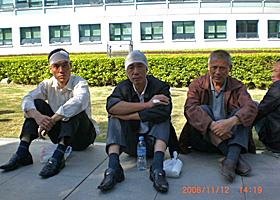 冲突期间,有工人被击中头部受伤,敷药后在街上坐下休息。