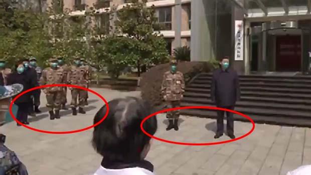 習近平站在報稱是「火神山醫院」的建築物前,但他的影子跟其他人的影子的方向並不一致。(網絡視頻截圖)