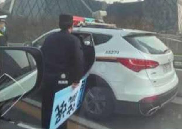 交警手持一塊沒收得來的紙牌,上面寫著「流氓下台」。(網絡圖片)