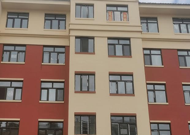 雙鴨山市康安嘉園一些房屋窗戶上都貼著售房信息,其中包括50平方米住房,售價1.2萬元人民幣。(證券時報圖片)