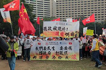 12月30日,香港撑梁游行队伍手持国旗、特区区旗以及横幅,在维园起步游行政府总部。(粤组记者文宇晴摄)