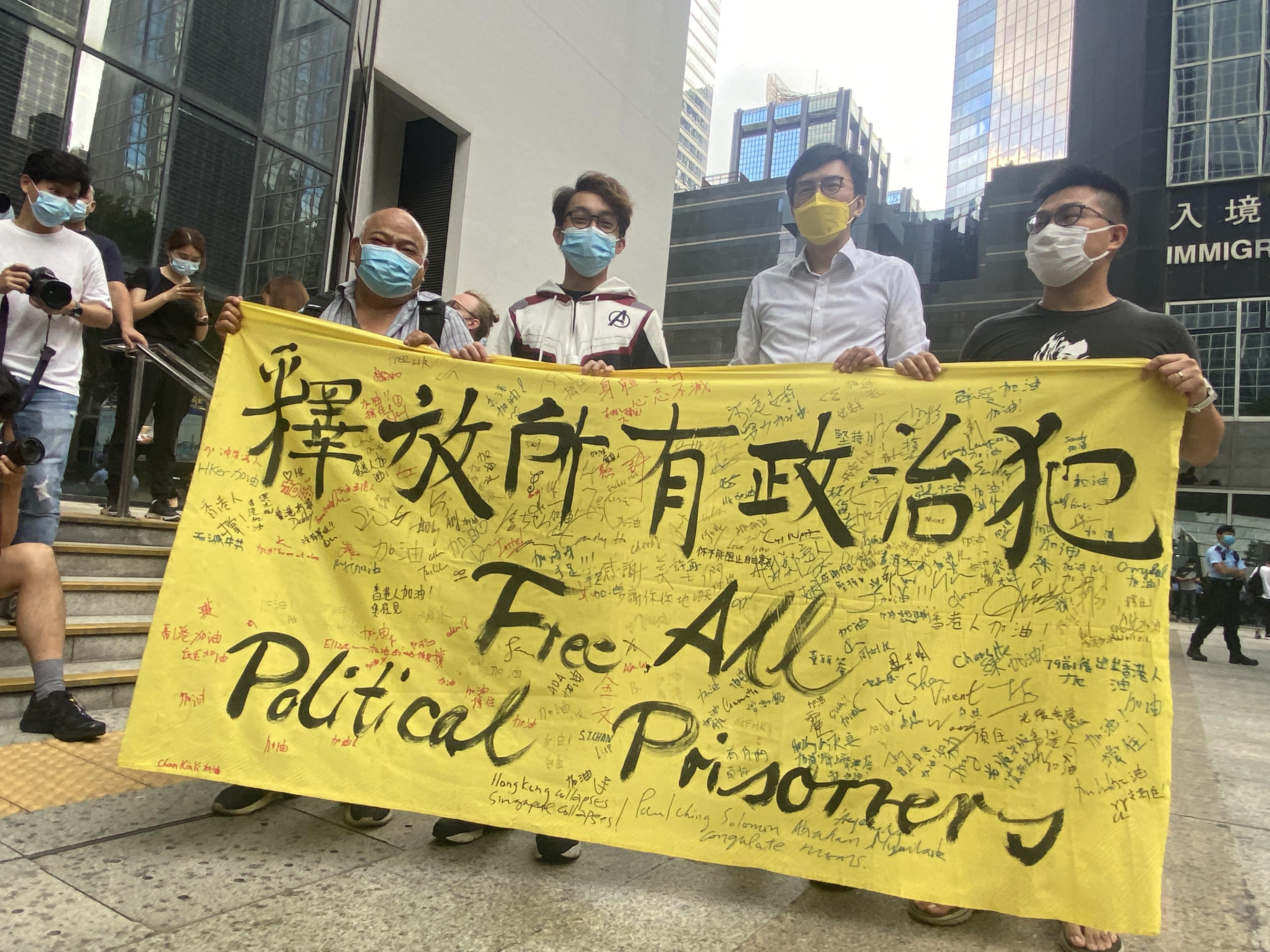 社民運吳文遠(右二)和民陣召集人陳皓桓(左二)等,在區域法院大樓外手持寫有「釋放所有政治犯」的橫額抗議。(李智智 攝)