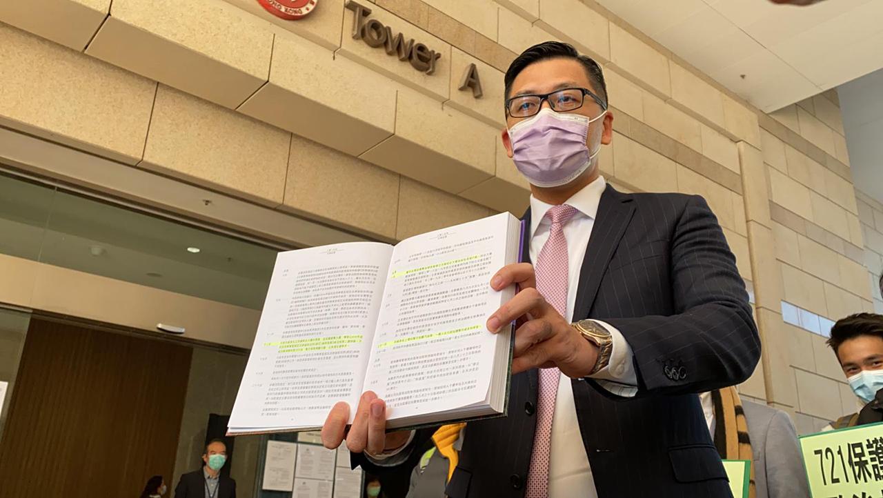 2020年12月21日,林卓廷上庭前展示一本港府2019年出版的年報,批評港府扭曲721歷史。(劉少風 攝)
