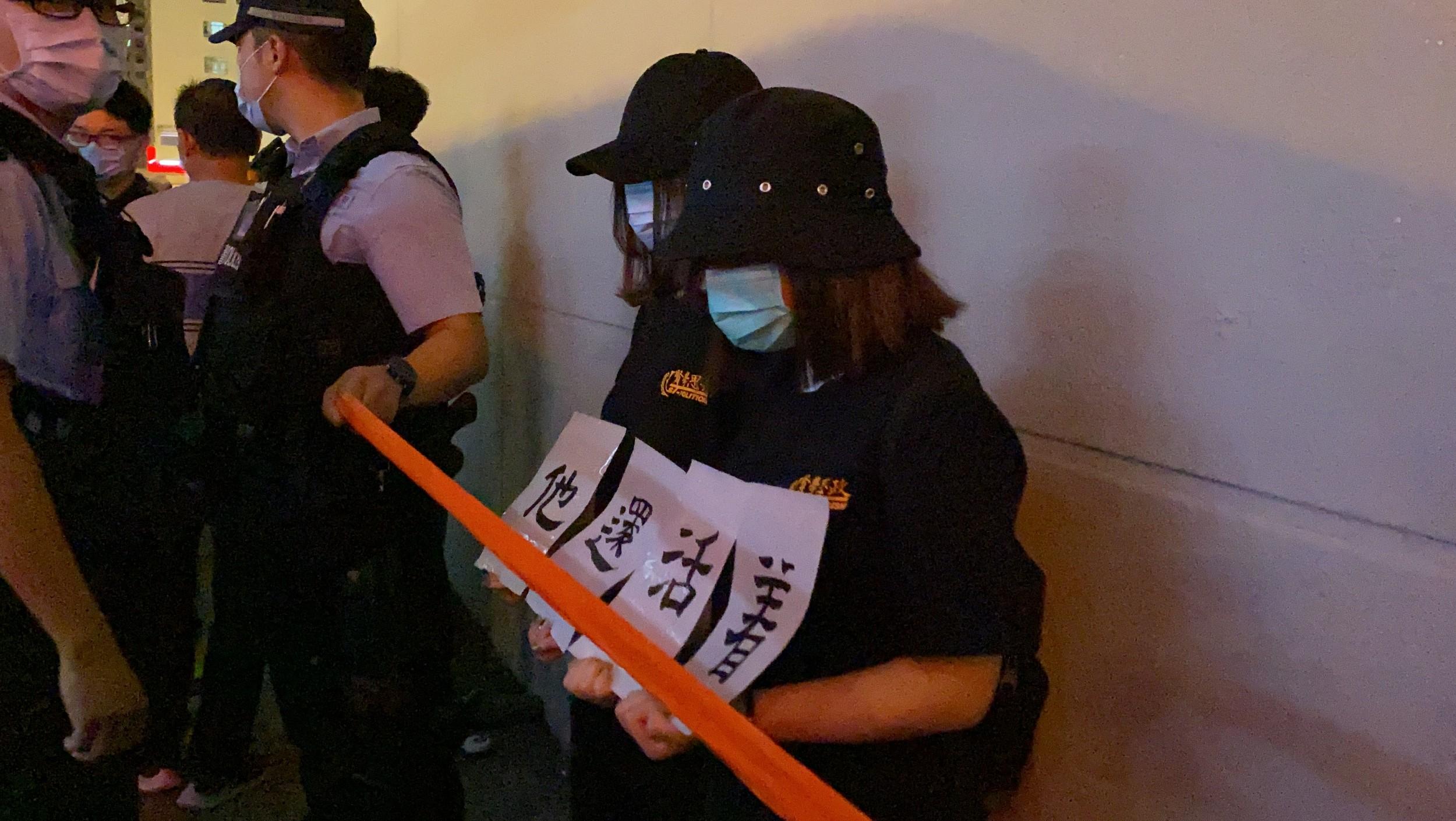 有市民举起标语,上书「有些人死了,但他们还活著」。(李智智 摄)