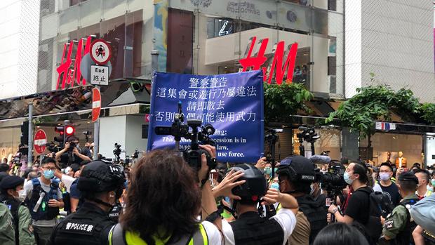 警方高举蓝旗指现场属非法集会。(文海欣 摄)