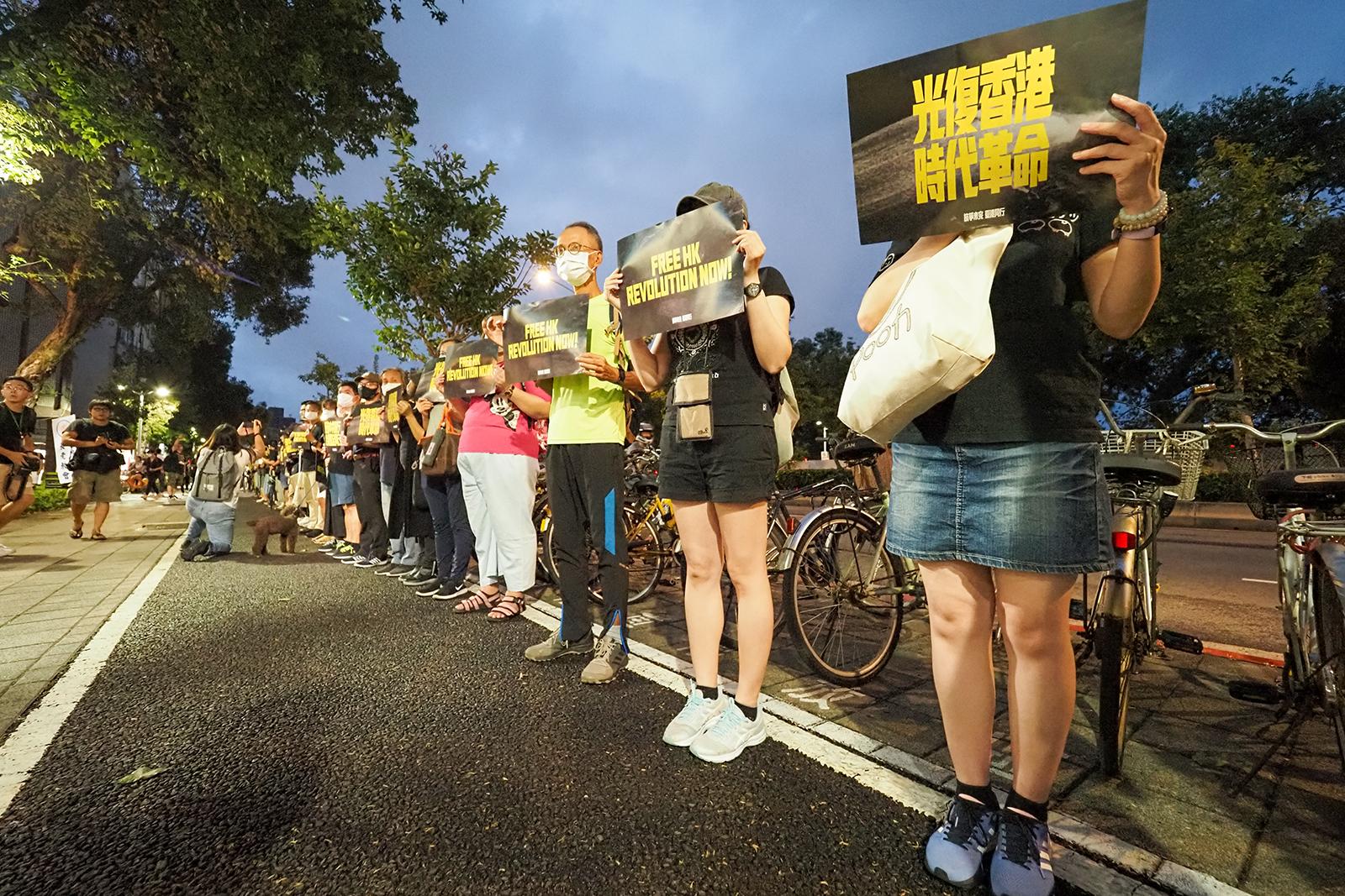 2020年8月31日,民眾在台灣大學對面馬路排成一列手持撐香港標語,人龍超過兩百公尺。(鍾廣政 攝)
