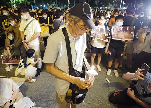 2020年6月4日,台湾铜锣湾书店店长林荣基,手持蜡蠋高唱悼念六四歌曲。(锺广政 摄)
