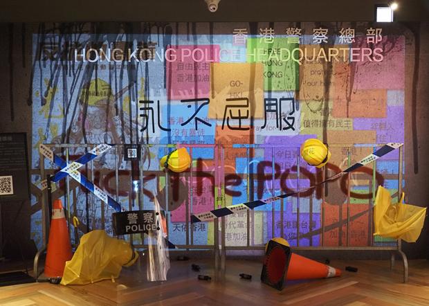 2020年6月24日,展覽其中一個主題,以數位連儂牆疊影在香港警察總部,表現出港警和中國的連結。(鍾廣政 攝)
