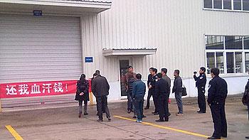 四川省安县十多名农民工代表,11月7日到国营企业的厂房外拉横额讨薪。(相片由六四天网提供)