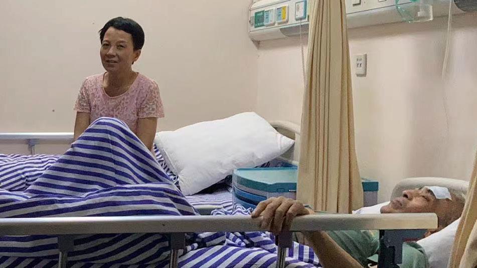 2021年7月9日,李旺玲(左)在湖南邵阳的肿瘤医院照料丈夫赵宝珠(右)。(陈玉华独家提供)
