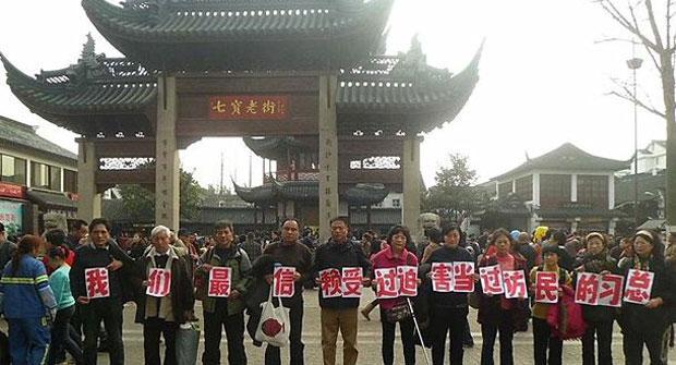 """2014年2月1日,数十上海访民,趁周六大年初二,集体到上海旅游景点七宝镇老街,向国家总书记习近平申冤。他们举起写有""""我们最信赖受过迫害当过访民的习总""""的标语,吸引大批旅客围观拍照。(访民摄)"""