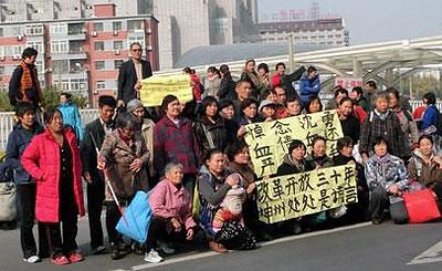 10月30日,在北京的數十名上海訪民集體到火車南站舉橫額,要求當局徹查沈勇死亡事件。(訪民提供)