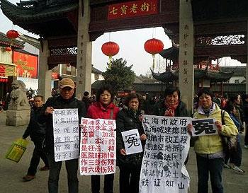 2013年2月13日,上海七名訪民包括吳玉芬、孔令珍、石萍、嚴燕文等人,大年初四手持狀紙和維權標語到當地著名景點七寶鎮維權拍照。(參與訪民提供)