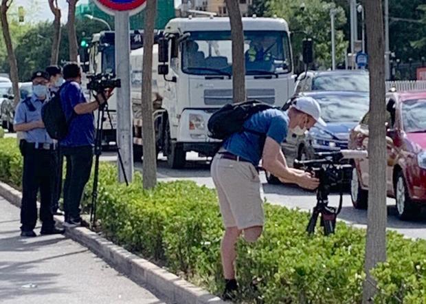 被拒采访的外媒记者在法院对开马路边拍摄,亦遭警察盘查。(小健 摄)