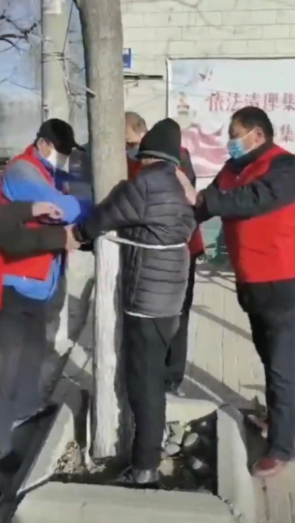 河北石家莊一居民外出,被看守人員捆綁在樹上。(視頻截圖)