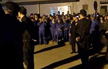 1月29日,廣州東海橡塑廠上千工人不滿年終獎金被削,連日在廠房內罷工抗議,警方介入事件,並派員攝錄員工樣貌。(網民提供)