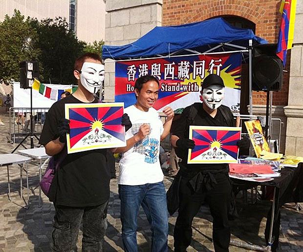 香港与西藏同行组织3月10日在尖沙咀举行纪念活动,戴面具青年手持雪山狮子旗图案拍照。(照片来自香港与西藏同行)