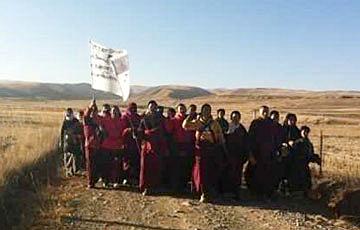青海海南州同德縣二十多名僧人及藏民,11月11日手持抗議橫幅,遊行四十公里至達塘谷鎮時,一度被拘押。(照片由維權人士提供)