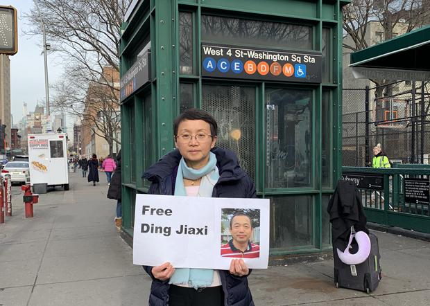 罗胜春在纽约街头高举要求中国当局释放丁家喜的标语。(罗胜春推特图片 / 2020年1月23日)
