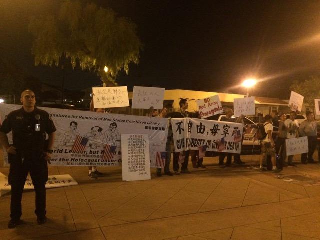 10月8日晚,美國洛杉磯蓋博市大劇院上演紀念紅軍長征80周年紅歌會,抗議人士在場外舉牌抗議。(涉美提供)