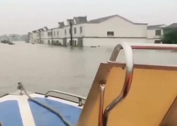 安徽安慶洪水淹沒居民二樓,居民借衝鋒舟回家。(網絡視頻截圖)