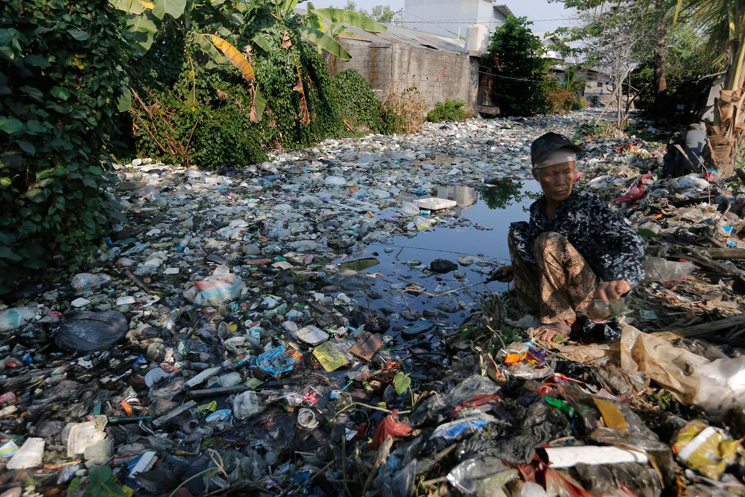 A scavenger collects plastic materials to be sold to recycling plants on the Bahagia river in Bekasi, Indonesia, Aug. 1, 2019.