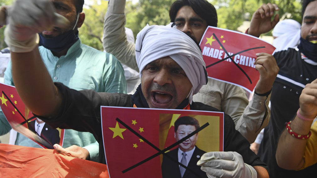 A demonstrator shouts slogans while holding a poster of Chinese President Xi Jinping during an anti-China protest near Chinese embassy in New Delhi, June 17, 2020.