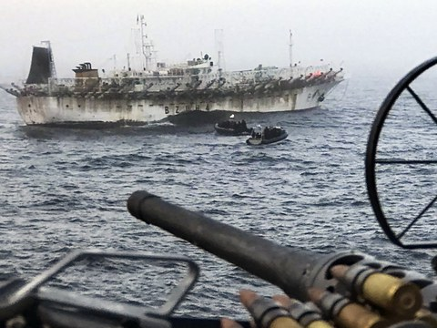China's fishing fleet ranges throughout the world's oceans. Here, a Chinese fishing vessel is placed under escort after being caught by an Argentine warship operating illegally within Argentina's exclusive economic zone.