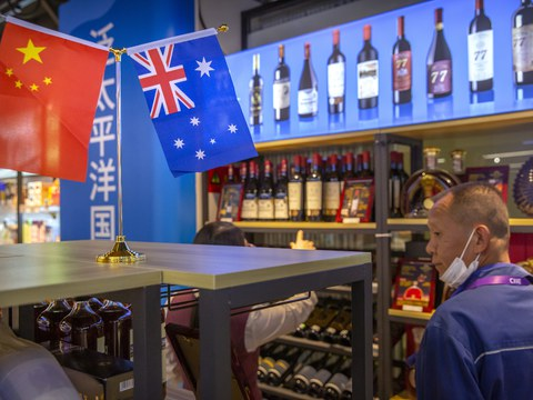 A visitor wearing a face mask to protect against the coronavirus looks at a display of Australian wines at the China International Import Expo (CIIE) in Shanghai on Nov. 5, 2020.