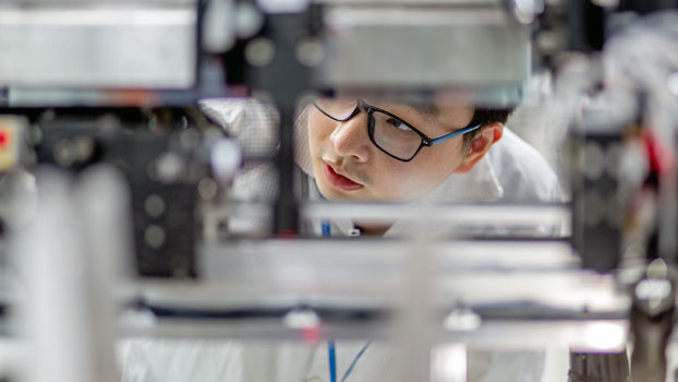 A worker examines equipment at the Guangdong Ruigu Optical Network Communications Co. Ltd., an optical component and transceiver manufacturer in Dongguan, southeast China's Guangdong province, May 7, 2019.