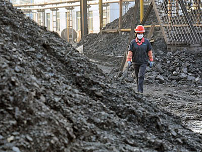 A Chinese worker walks past piles of coal in a coalyard at a mine in Huaibei, eastern China's Anhui province, Nov. 7, 2016.
