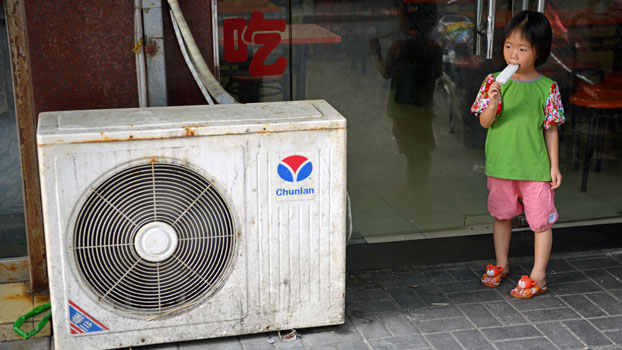 A young girl eats an popsicle while standing next to an air conditioning unit during a heat wave in Shanghai, China, in a file photo.