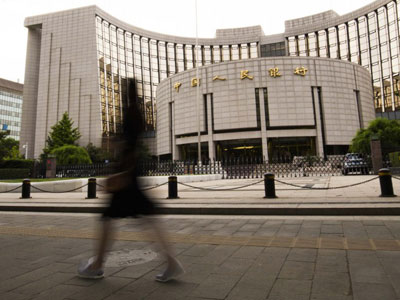A pedestrian walks past the headquarters of the People's Bank of China (PBOC), China's central bank, in Beijing, May 4, 2016.