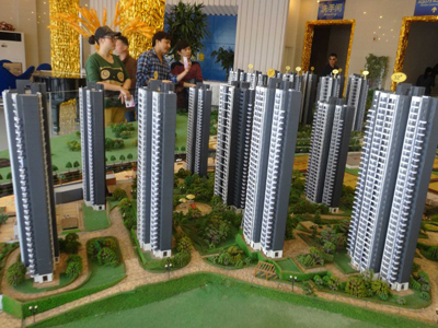 Chinese homebuyers look at housing models of a residential property project in Yichang, central China's Hubei province, March 6, 2016.
