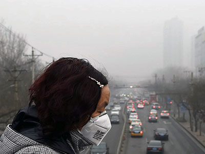 A Chinese woman wears a face mask on a heavily polluted day in Beijing, Dec. 26, 2015.