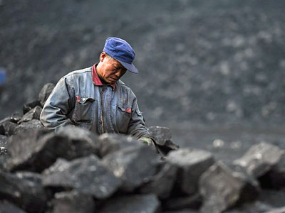 A Chinese worker sorts coal on a conveyor belt near a coal mine in Datong, northern China's Shanxi province, Nov. 20, 2015.