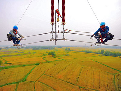 Chinese workers mount high-voltage cables over massive fields in Fengyang county of Chuzhou city in eastern China's Anhui province, May 22, 2014.