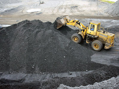 A wheel loader piles up coal at a coalyard in Yichang, central China's Hubei province, Sept. 12, 2016.